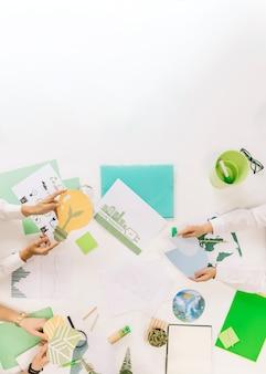 Gruppe wirtschaftler, die energiesparende ikonen über schreibtisch halten