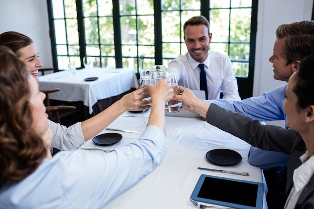 Gruppe wirtschaftler, die glas wasser im restaurant rösten