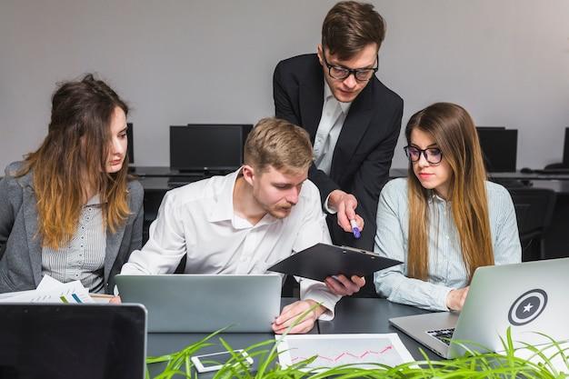 Gruppe wirtschaftler, die laptop beim arbeiten an dokument verwenden