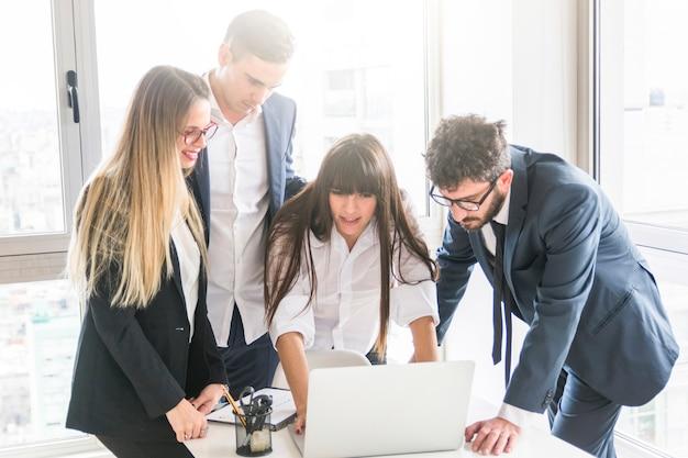 Gruppe wirtschaftler, die laptop im büro betrachten