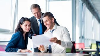 Gruppe Wirtschaftler, die Unternehmensplan im Büro betrachten