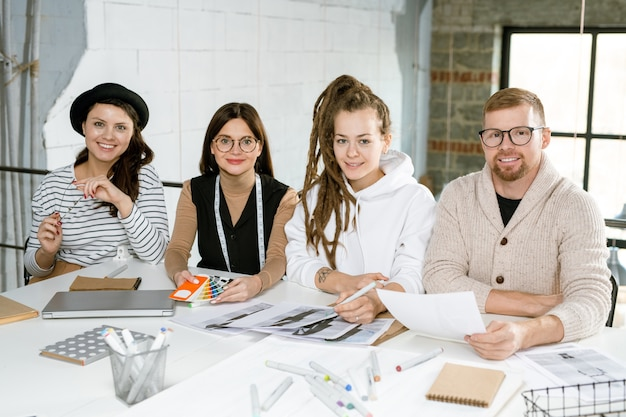 Gruppe zeitgenössischer kreativer modedesigner, die am schreibtisch sitzen, während sie über neue kollektion beim treffen arbeiten
