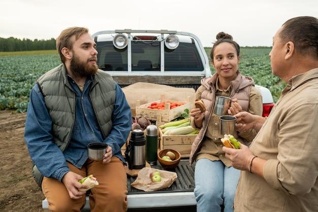 Gruppe zeitgenössischer landwirte, die sich ausruhen und einen snack mit getränken zu sich nehmen