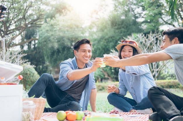 Gruppen des jungen jugendlich, die spaßpicknick im park zusammen haben.