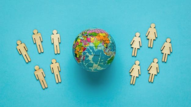 Gruppen von männern und frauen aus holz und ein modell der welt auf blauem grund. das konzept des umweltschutzes.