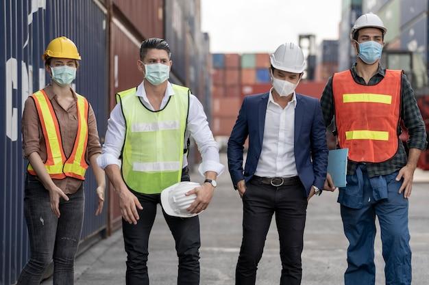 Gruppenarbeiter trägt schutzmaske gesicht und schutzhelm und anzug sicherheitskleid