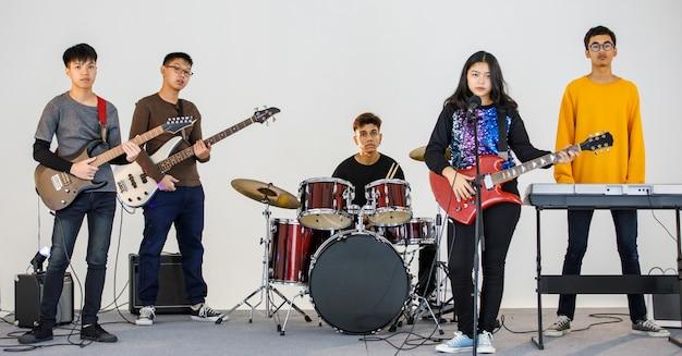 Gruppenaufnahme von fünf jugendlichen musikern, die die musik spielen und zusammen ein lied singen. junge studenten spielen bassgitarre, e-gitarre, schlagzeug und keyboard. konzept eines teenagers, der mit freunden spielt