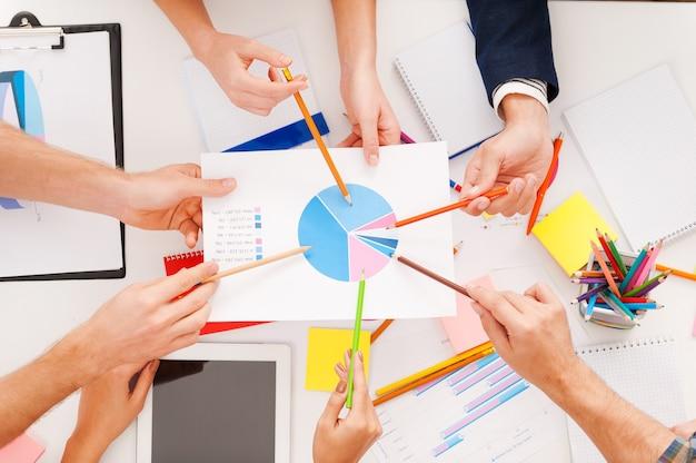 Gruppendiskussion. draufsicht von geschäftsleuten, die beim sitzen am tisch auf diagramme zeigen
