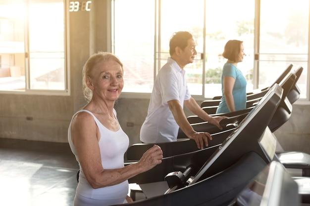 Gruppenfreund des älteren läufers an der turnhalleneignung lächelnd und glücklich. älterer gesunder lebensstil.