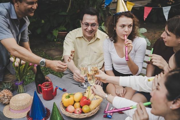 Gruppenfreunde von senioren und jungen glücklich und spaß in der partei mit garten des champagners zu hause