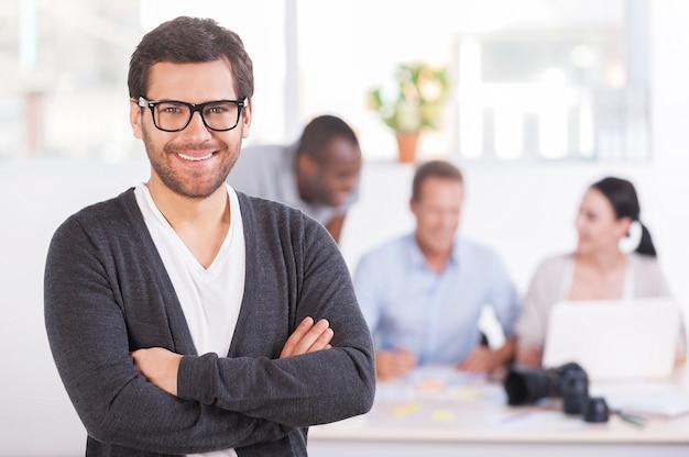 Gruppenführer. schöner junger mann mit brille, der die arme verschränkt hält und lächelt, während drei leute am hintergrund arbeiten
