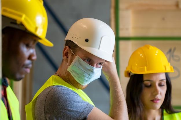 Gruppenlagerarbeiter, die schutzmaske tragen, die in der industriefabrik oder im lager arbeitet.