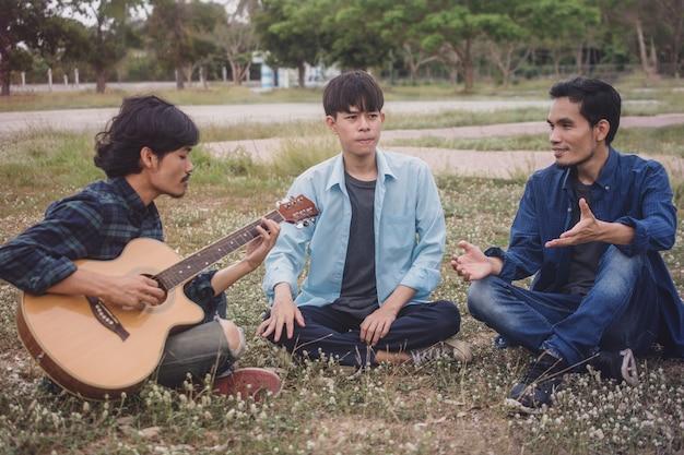 Gruppenleute asiatischer mannfreunde, die gitarre im freien spielen