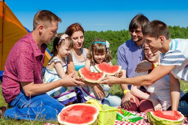 Gruppenporträt im freien der glücklichen familie, die picknick auf grünem gras im park und wassermelone genießt