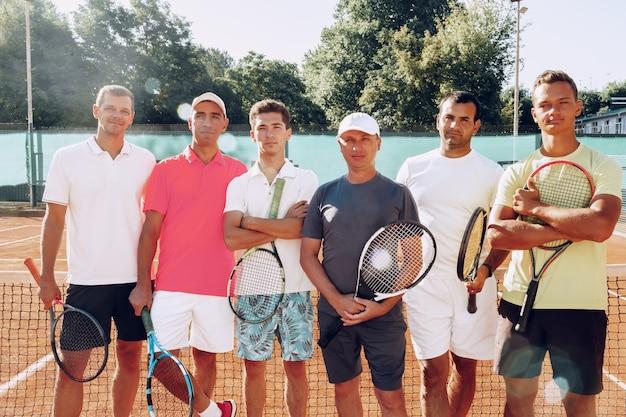 Gruppenporträt von sechs männlichen tennisspielern, die auf platz stehen