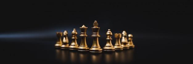 Gruppenschachgoldfarbbrettspiel auf schwarzem hintergrund
