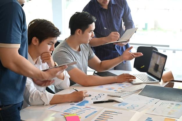 Gruppensitzung des jungen mannes des startgeschäfts und brainstorming auf büroarbeitsplatz.
