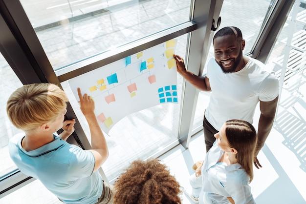 Gruppentraining. fröhliche junge berufskollegen, die im büro stehen und an dem projekt arbeiten, während sie die gruppenarbeit genießen