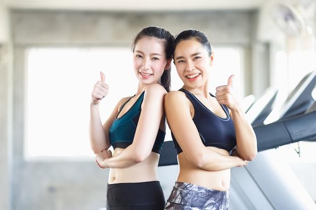 Gruppieren sie die attraktive asiatische frau, welche die muskeln ausdehnt und nach übung, training, eignung am turnhallenclub sich entspannt. frohes lächelndes mädchen der sporterholung ist genießen mit ihrem trainingsprozeß.