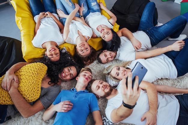 Gruppieren sie die schönen jungen leute, die das selfie tun, das auf dem boden liegt, die mädchen und jungen der besten freunde, die zusammen spaß haben und emotionalen lebensstil aufwerfen