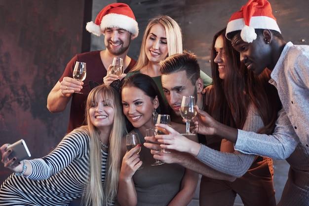 Gruppieren sie die schönen jungen leute, die selfie in der partei des neuen jahres, in den mädchen und in den jungen der besten freunde tun, die zusammen spaß haben und emotionale lebensstilleute aufwerfen. hüte santas und champagnergläser in ihren händen
