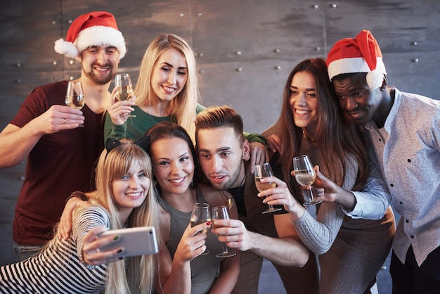 Gruppieren sie die schönen jungen leute, die selfie in der partei des neuen jahres, in den mädchen und in den jungen der besten freunde tun, die zusammen spaß haben und lebensstilleutekonzept aufwerfen. hüte santas und champagnergläser in ihren händen