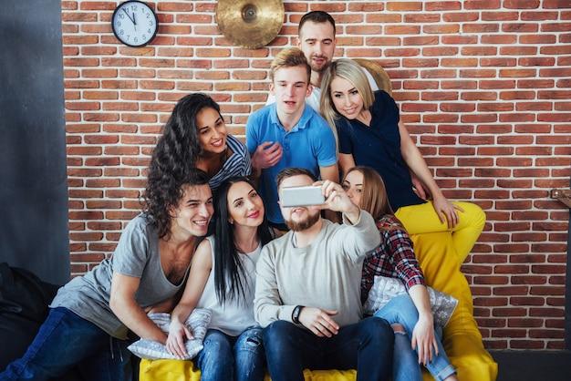 Gruppieren sie die schönen jungen leute, die selfie in einem café, in mädchen und in jungen der besten freunde tun, die zusammen spaß haben und emotionalen lebensstil aufwerfen