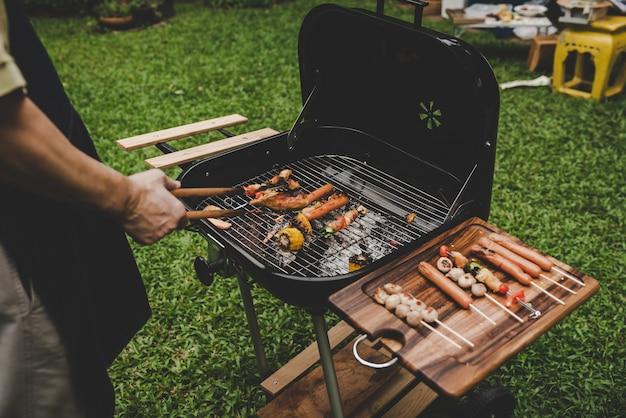 Gruppieren sie freunde des älteren grills auf dem grill im garten der partei zu hause kochend