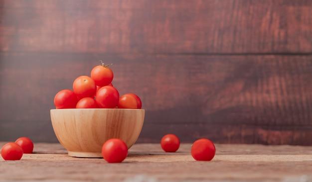 Gruppieren sie reife tomate in einem hölzernen schüsselplatz auf dem holztisch