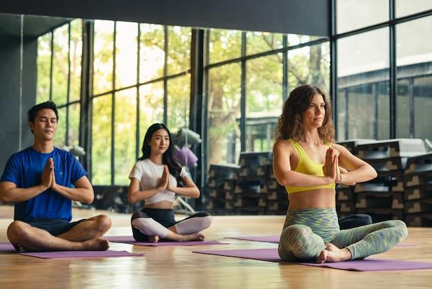 Gruppieren sie übendes yoga der frau und des mannes und meditiert in der eignungsklasse