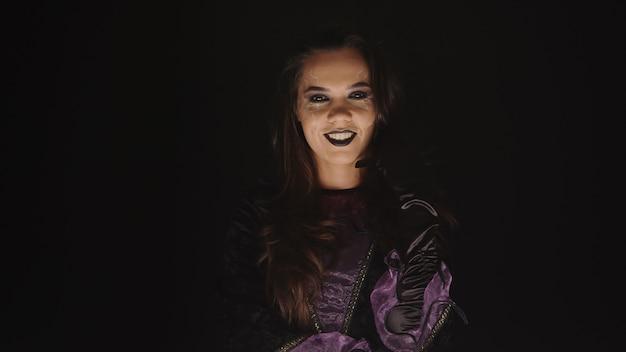 Gruselige frau, die sich für halloween wie eine hexe auf schwarzem hintergrund verkleidet hat