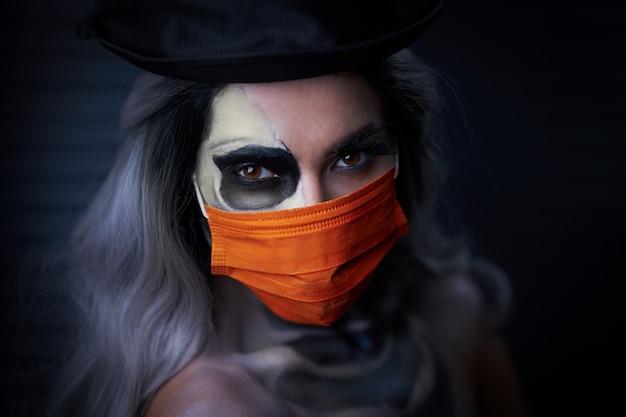 Gruselige frau in halloween-gothic-make-up mit gesichtsmaske aufgrund von covid-19-beschränkungen mask