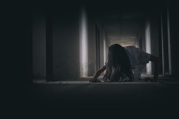 Gruselige geisterfrau dunkel im spukhaus-halloween-thema streckt sich aus und blut