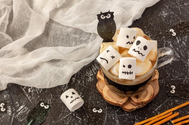 Gruselige gesichter (monster) von marshmallows in einer tasse kaffee für halloween