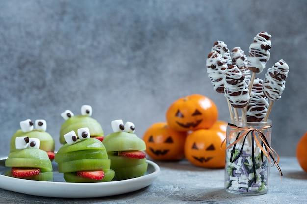 Gruselige grüne kiwi-monster für die halloween-party