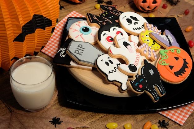 Gruselige halloween-kekse neben einem milchglas