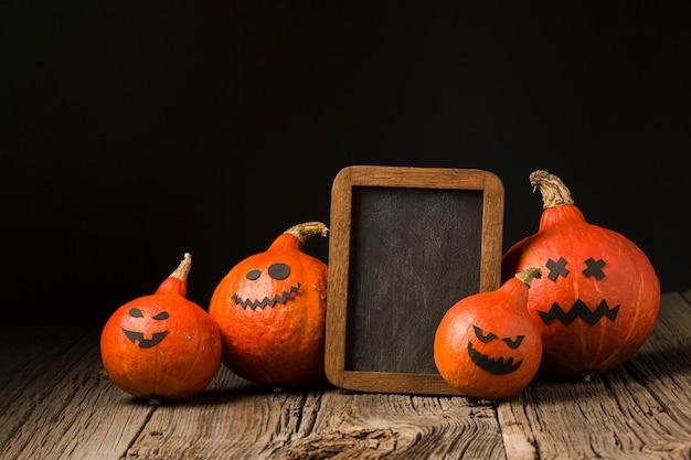 Gruselige halloween-kürbise mit modellrahmen