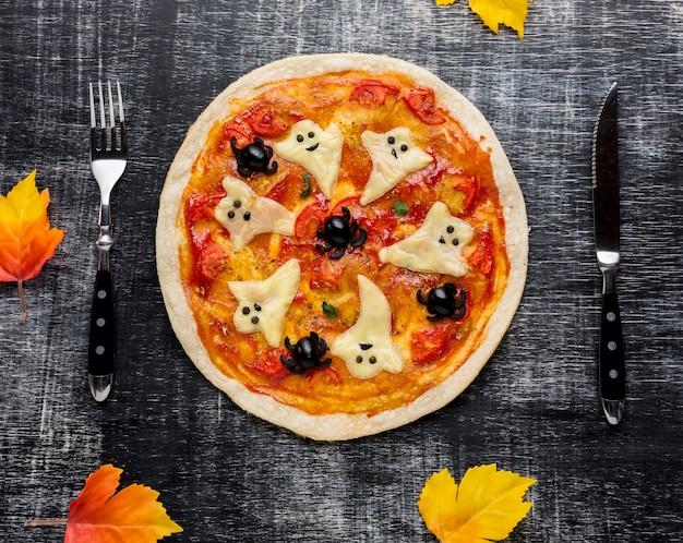 Gruselige halloween-pizza mit tischbesteck