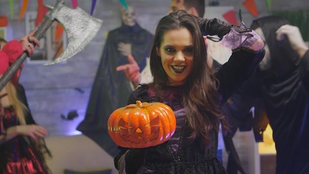 Gruselige hexe, die halloween mit ihren freunden feiert, die wie verschiedene gruselige monster in einem dekorierten raum verkleidet sind
