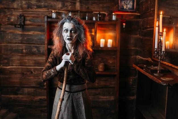 Gruselige hexe mit einem stock am spiegel und kerzen