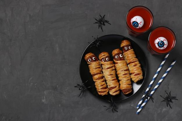 Gruselige wurstmumien und tomatensaft für halloween-party auf dunklem teller, ansicht von oben. flach liegen. platz für text.