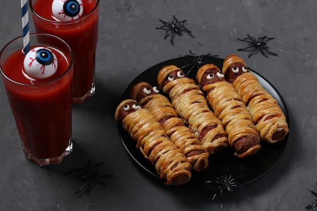 Gruselige wurstmumien und tomatensaft für halloween-party auf schwarzem teller.