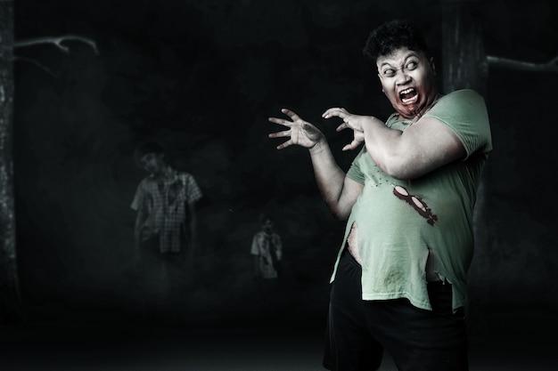 Gruselige zombies mit blut und wunde an seinem körper, die im dunklen hintergrund laufen