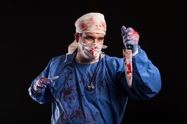 Gruseliger arzt mit bösem gesicht, der sein messer im studio betrachtet. mann verkleidet sich wie ein killerdoktor für halloween.