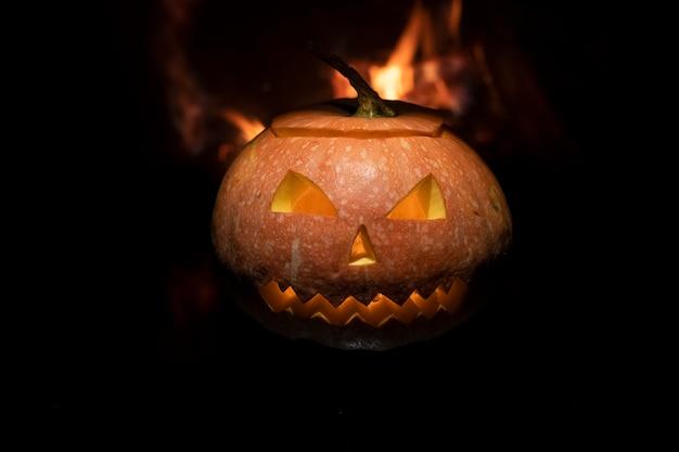 Gruseliger halloween-kürbis nahe einem kamin. feuer im hintergrund.