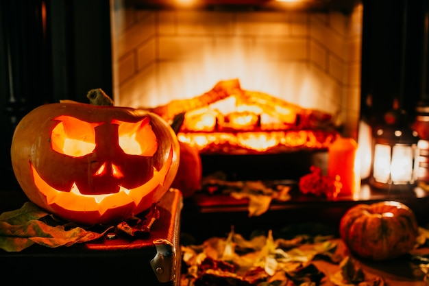 Gruseliger halloween-kürbis nahe einem kamin. feuer und trockene blätter auf dem hintergrund. jack of the lantern, exemplar. schießen sie im dunkeln.
