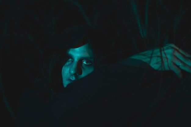 Gruseliger mann mit der haube, die in der dunkelheit sitzt