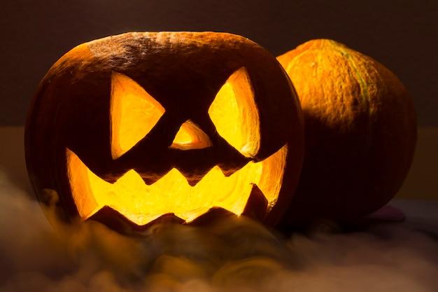 Gruseliger orange halloween kürbis mit dem rauch auf dem dunklen hintergrund