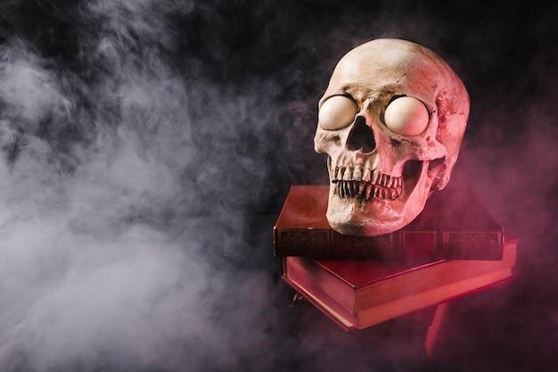 Gruseliger schädel auf bücherstapel im rauche