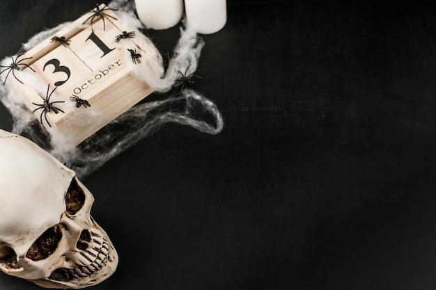 Gruseliger schädel mit hölzernem datum und plastiknetz